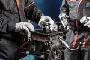 car restoration technicians dissembling a classic car engine