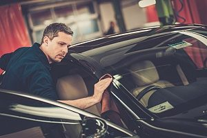 worker applying custom auto body shop techniques to a car