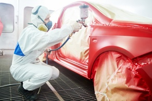 Man increasing clients car sale value with custom paint job