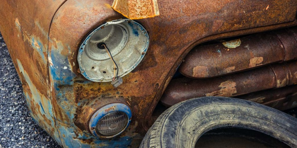a rusty vintage car owned by a man who learned how to repair rust on a car