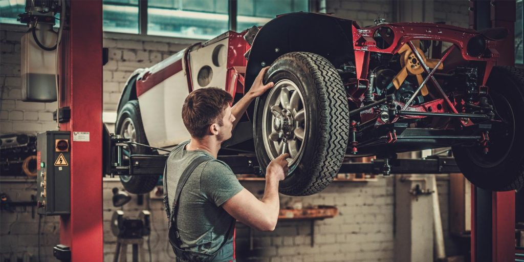 Car mechanic working with car in the air