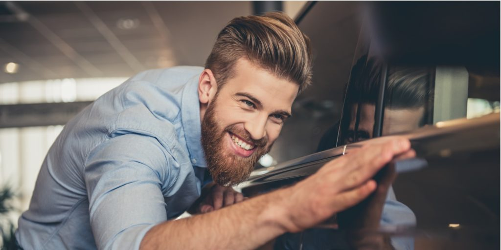 A bearded man is stroking his just bought classic car.