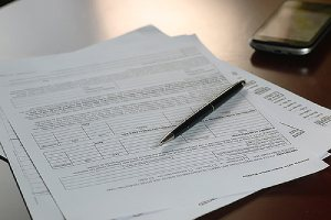 A pen and some documents on a desk.If you are buying a classic car, make sure to check the vehicle title carefully.