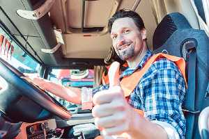 A truck driver in driving seat giving thumbs-up. For truck frame restoration reach out to the experts