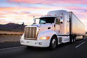 A truck on a highway at sunset. Truck frame restoration is the solution to rusting and damaged truck frame.