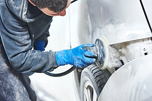 a mechanic sanding the outside of a car in a partial restoration at an auto body shop