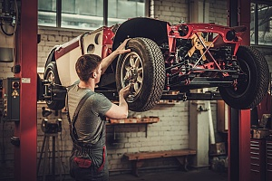 an auto mechanic performing a full car restoration at an auto body shop