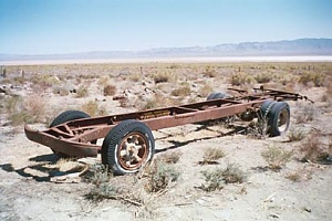 an old rusted truck frame in the middle of a desert