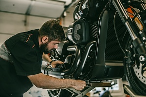 man assessing how much it is going to be to fix a custom motorcycle