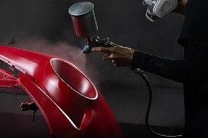 A custom auto body mechanic applying red paint on a bumper