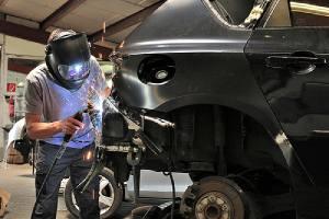 A custom auto body mechanic welding car body