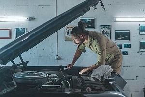 a man working on a car at a custom auto body shop
