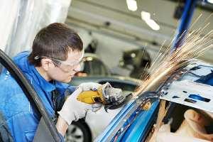 Custom auto restoration worker grinding sheet metal welded to car door frame