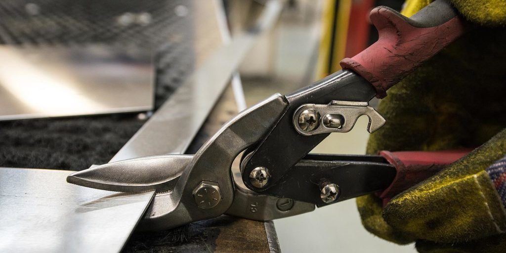 Cutting a car restoration sheet metal with powerful industrial hand-operated scissors