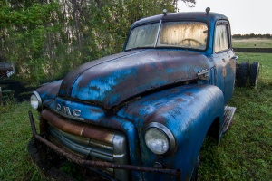 a blue truck before being worked on with some rust