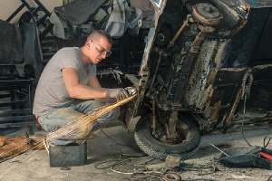 A mechanic restoring a classic car