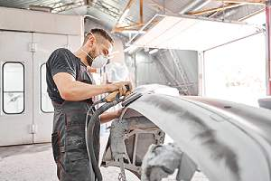 Mechanic repairing rust damaged section of a car