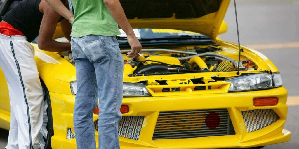 two young male car enthusiasts looking at the engine of a car and at automotive show